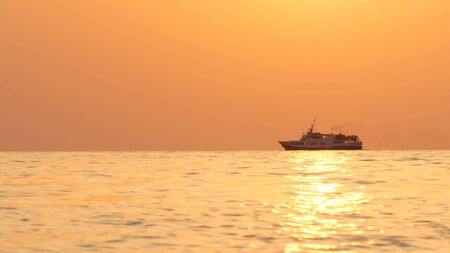 A passenger ship sails the sea on the horizon during sunset
