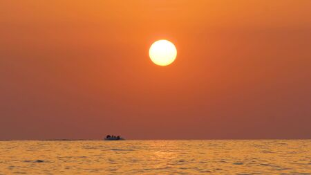 A boat with people sailing on the sea on the horizon at high speed during sunset
