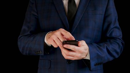 Close-up. A male businessman in a beautiful suit is working using a smartphone, touching the touch screen 스톡 콘텐츠