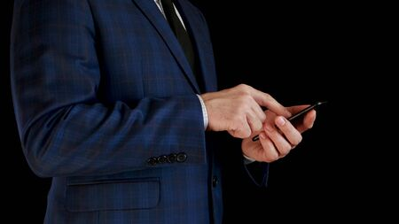 Close-up. Side view. Male businessman in a beautiful suit working using a smartphone, touching the touchscreen