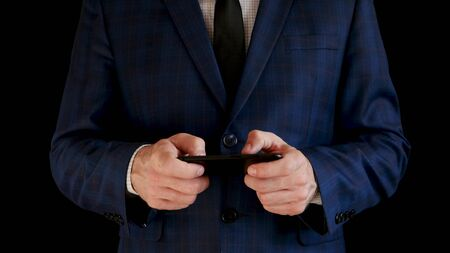 Businessman in suit works with a smartphone, touches the touch screen of the phone on a black background. 스톡 콘텐츠