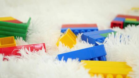 Color blocks toys lie on a white background close-up. Camera slider movement.