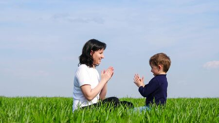Mother and small child sit on the green grass and play, slapping each others hands.