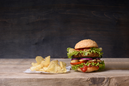 Delicious burger with beef, tomato, cheese, lettuce and potato chips on wooden counter. Copy space.