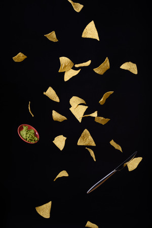 tortilla de maiz: Nachos chips de tortilla de maíz con salsa de guacamole fresco del vuelo, fondo negro. Foto de archivo
