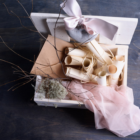 ceramic heart: Romantic wedding background. Vintage scrolls, envelopes, ceramic heart with pink silk lace in white wooden box.