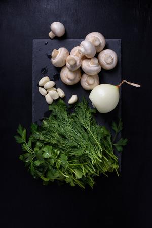 mushroom: Spring vegetables on slate board, black background. Champignon mushrooms, garlic, onion, dill, parsley and cilantro, top view. Foto de archivo