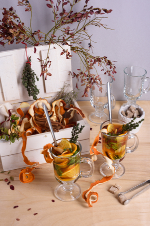 orange peel clove: Tea with herbs, oranges and cinnamon on wooden table. Stock Photo