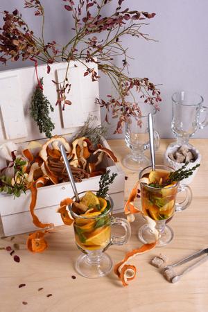 orange peel clove: Tea with herbs, oranges and cinnamon on wooden table. Stock Photo