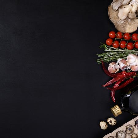 restaurante italiano: ingredientes vegetales frescos en el fondo oscuro. La comida vegetariana, la salud o el concepto de la cocina. Vista superior y el espacio para el texto.