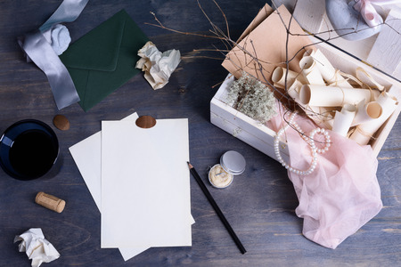 writing paper: Still life details. Paper scrolls and pearls in retro vintage wooden box. Romantic love letter or wedding invitations writing template on wooden table.