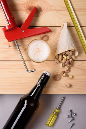 alcohol screwdriver: Bottle of beer, pistachio nuts and work tools on wooden planks. Flat lay, top view.