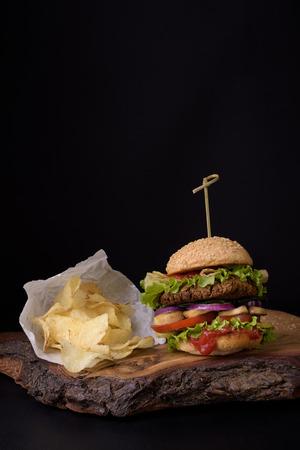 woden: Homemade burger with potato chips on rough woden board, dark background.