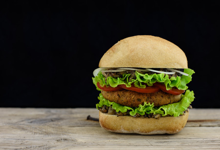 gastronome: Juicy burger on wooden board.