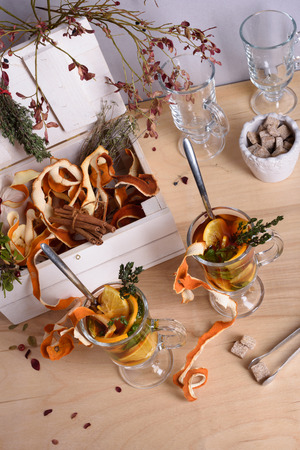 orange peel clove: Two Glasses of hot mulled wine with orange slices, cinnamon, thyme on wooden table. Warming drink with ingredients. Stock Photo