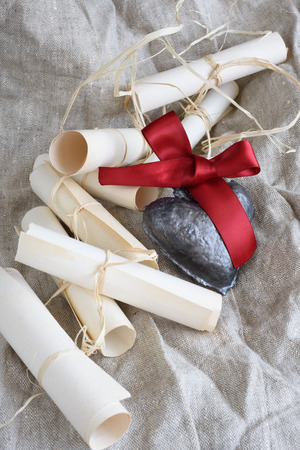 ceramic heart: Parchment wedding scrolls and ceramic heart with crimson ribbon on a rustic cloth.