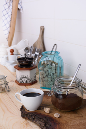 blend: Ground coffee blend and brewed black coffee. Wooden buffet table full of utensil. Light background.
