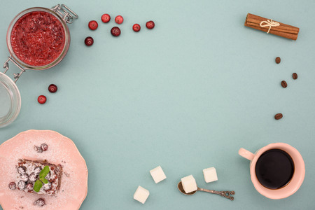 Coffee and chocolate cake with cranberry jam and cinnamon on wooden board, over turquoise background. Top view, copy space.