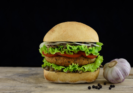gastronome: Juicy burger on wooden board with garlic, copy space.
