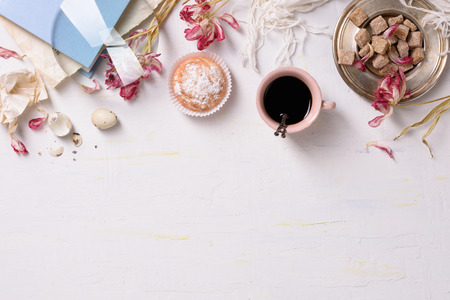 Breakfast background: cup of coffee, cakes, brown sugar and flowers, over white. Top view, copy space.