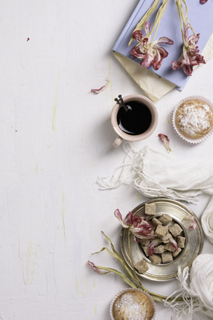 Coffee and vanilla cupcakes with pink tulip flowers over white background, top view. Reklamní fotografie