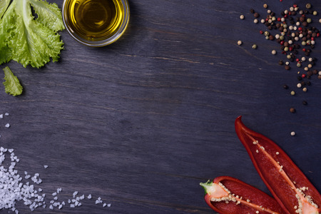 Salad with seasoning ingredients - spices, red pepper, olive oil and salt, food frame. Top view, copy space.