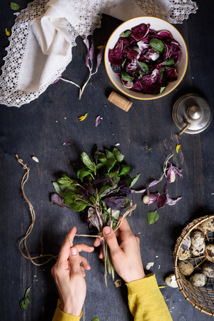 woman cooking: Person preparing healthy herbal salad with basil, radicchio and quail eggs. Rustic wooden table, view from above.