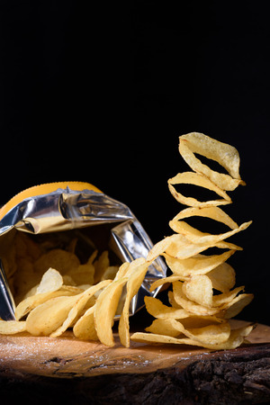 opened bag: Heap of golden potato chips with an opened bag on wooden table, close-up.