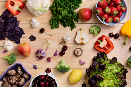 gastronome: Variety of colorful fruits, vegetables and berries. Healthy diet concept. Vegetarian organic food set over wooden table. Top view.