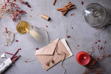 burning love: Invitation or love letter, glass of wine, burning candle and aromatic sticks. Valentines day or Weding day background. Stock Photo