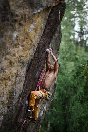 struggles: Male rock climber struggles to reach his next grip on a steep cliff. Extreme sport. Stock Photo
