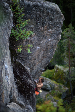 struggles: Male rock climber struggles to climb a challenging overhanging. Extreme sport climbing. Stock Photo