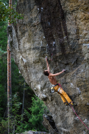belay: Rock climber, professional athlete, climbing in Karelian mountains. Extreme sports.