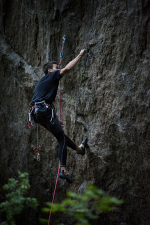 struggles: Rock climber dangles in midair as he struggles to climb a challenging cliff. Stock Photo