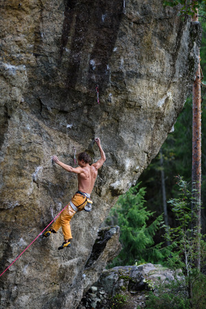 struggles: Outdoor sport. Rock climber struggles to climb a challenging cliff.