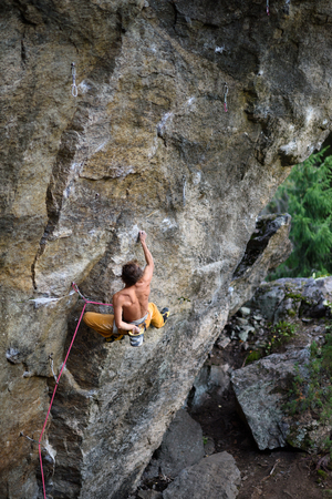 struggles: Outdoor sport. Rock climber dangles in midair as he struggles to climb a challenging cliff. Stock Photo