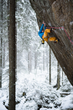Outdoor winter sport Rock climber ascending a challenging cliff Extreme sport climbing Stock Photo