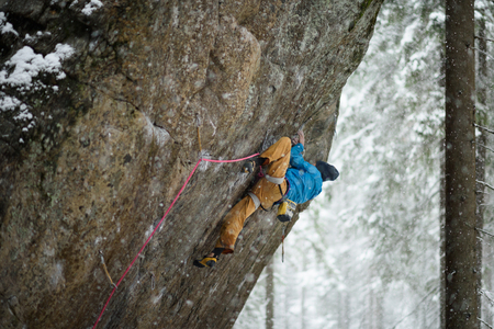 ascent: Rock climber on a challenging ascent. Extreme climbing. Unique winter sports. Scandinavian nature.