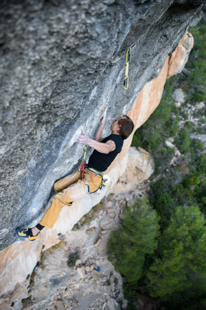 Outdoor activity. Extreme rock climbing lifestyle. Male rock climber on a cliff wall. Siurana, Spain.