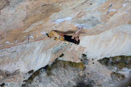 Rock climber ascending a challenging cliff. Extreme sport climbing. Freedom, risk, challenge, success Stock Photo