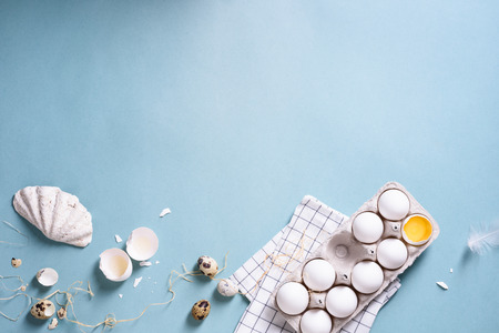 Chicken white eggs in a shell, egg yolk, quail eggs over turquoise background. Cooking concept, spring easter poster. Top view, copy space.