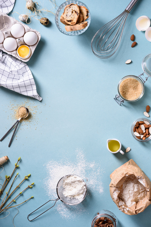 Bakery background frame. Fresh cooking ingredients - egg, flour, sugar, butter, nuts over blue background. Spring cooking theme. Top view, copy space. Stock Photo