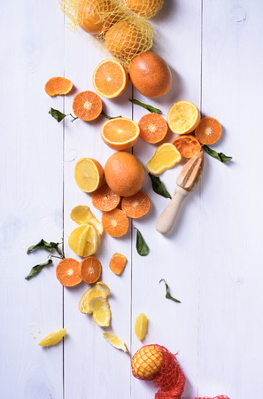 Fresh oranges, slices of orange fruits for making juice. Ripe citrus fruits with juice squeezer. Top view.