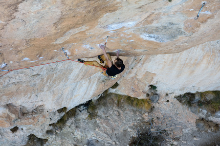 belay: Extreme sport climbing. Rock climber struggle for success. Outdoor lifestyle. A person trying hard to reach sucsess. Spain, Siurana