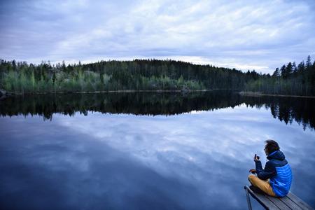 peace pipe: Young man sitting on a lake shore, smoking pipe. beautiful scandinavian nature.