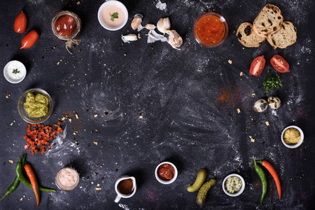 Sauces, appetizers and cooking ingredients, food frame background on messy dark table. Top view, copy space. Zdjęcie Seryjne - 85232541