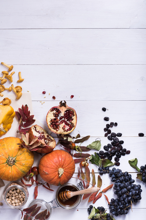 Seasonal autumn vegetables, squashes, mushrooms, honey and beans on white wooden table. Vegetarian feast. Top view, copy space. Stock Photo