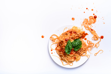 Italian pasta on a plate, spaghetti cooked with tomato sauce and spinach. White table, above view, copy space.