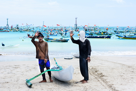 Travel destinations, island culture. Two local balinese fisherman, traditional boat and a catch on the beach. Ocean and a fishing fleet on the background. Kelan beach, Bali, Indonesia 11 October 2016 Editorial