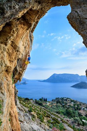Picturesque island view, young man climbing a rock. Travel destination Kalymnos, Greece.